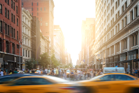 Foto de Fast paced motion in New York City as yellow taxi cabs speed down 5th Avenue with crowds of busy people walking across the intersection at 23rd Street in Manhattan with sunset light in the background - Imagen libre de derechos
