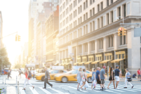 Foto de Crowds of anonymous people walking across an intersection on 5th Avenue in Manhattan New York City with colorful sunlight background - Imagen libre de derechos