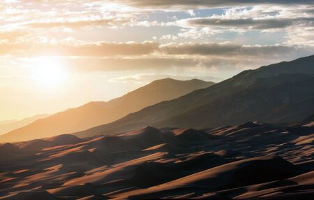 Photo for Sunlight shining over Great Sand Dunes National Park in the Colorado Rocky Mountains landscape scene - Royalty Free Image