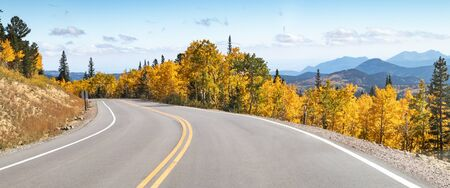 Photo pour Empty road winds through a panoramic mountain landscape scene with golden fall aspen trees in the Colorado Rocky Mountains - image libre de droit