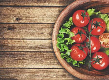 Foto de wooden bowl with cherry tomatoes - Imagen libre de derechos
