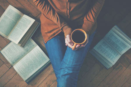 Photo pour girl having a break with cup of fresh coffee after reading books or studying - image libre de droit