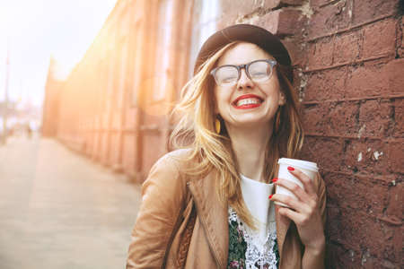 Photo pour Cheerful woman in the street drinking morning coffee in sunshine light - image libre de droit