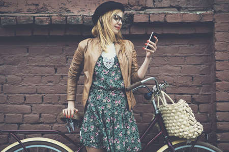 Foto de City lifestyle stylish hipster girl with bike using a phone texting on smartphone app in a street - Imagen libre de derechos