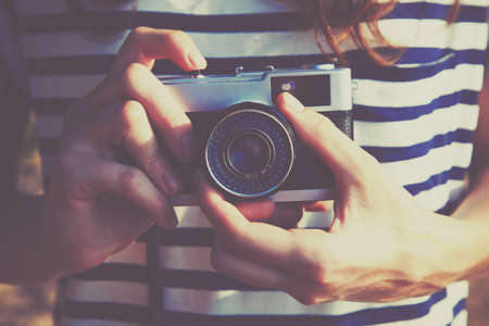 Photo pour girl holding retro camera and taking photo - image libre de droit