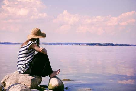 Foto de stylish woman alone sitting on stone coast and looking at sea - Imagen libre de derechos