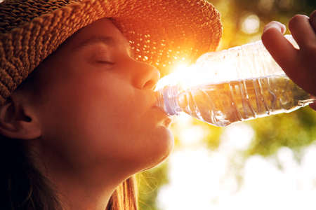 Foto de Woman drinking water in summer sunlight - Imagen libre de derechos