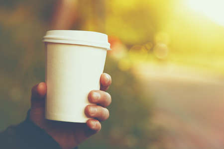 Foto für hand holding paper cup of coffee on natural morning background - Lizenzfreies Bild
