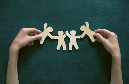 Foto de Wooden little men holding hands on blackboard background. Symbol of friendship, love or teamwork concept - Imagen libre de derechos