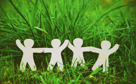 Photo for Wooden little men holding hands in summer grass. Symbol of friendship, family, teamwork or ecology concept - Royalty Free Image