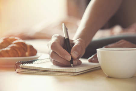 Photo pour female hands with pen writing on notebook with morning coffee and croissant - image libre de droit