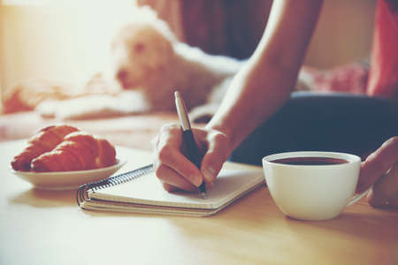 Foto de female hands with pen writing on notebook with morning coffee and croissant - Imagen libre de derechos