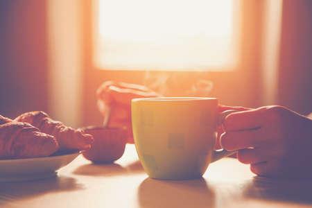 Foto de fresh breakfast with hot coffee and croissant in morning sunlight - Imagen libre de derechos