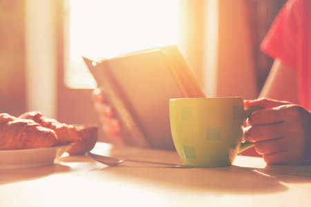 Photo pour fresh breakfast with hot coffee and reading book in morning sunlight - image libre de droit