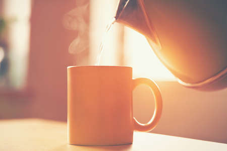 Photo pour kettle pouring boiling water into a cup in morning sunlight - image libre de droit