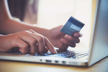 Photo pour Hands holding credit card and using laptop. Online shopping - image libre de droit