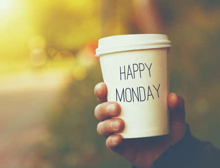 Foto de hand holding paper cup of coffee with Happy Monday motivational text on natural morning background - Imagen libre de derechos