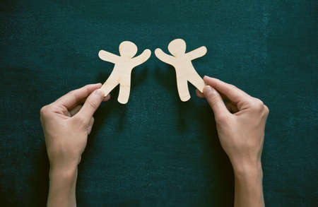 Photo pour Hands holding little wooden men on blackboard background. Symbol of friendship, love or teamwork concept - image libre de droit