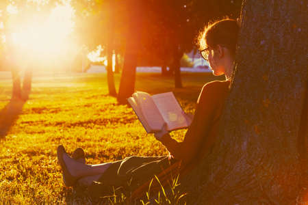Photo pour girl reading book at park in summer sunset light - image libre de droit