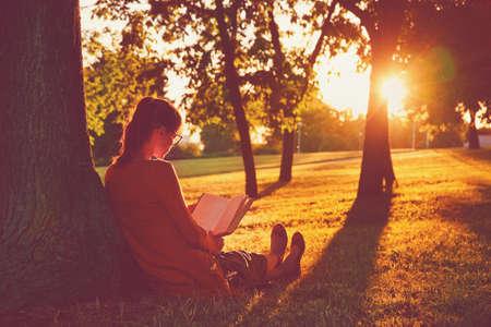 Foto de girl reading book at park in summer sunset light - Imagen libre de derechos