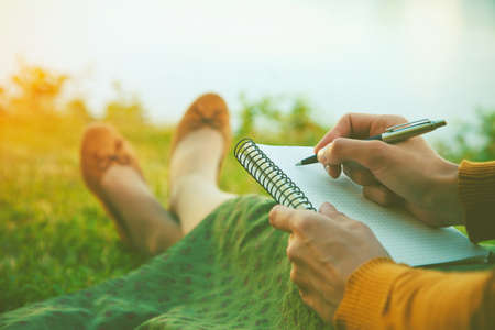 Photo for female hands with pen writing on notebook on grass outside - Royalty Free Image