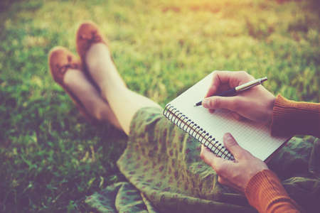 Photo pour female hands with pen writing on notebook on grass outside - image libre de droit