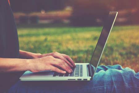 Foto de Hands using laptop and typing outside on nature background - Imagen libre de derechos