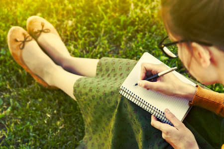 Photo pour girl with pen writing on notebook on grass outside - image libre de droit