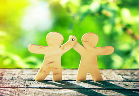Foto de Wooden little men holding hands on natural green background. Symbol of friendship, ecology and teamwork - Imagen libre de derechos