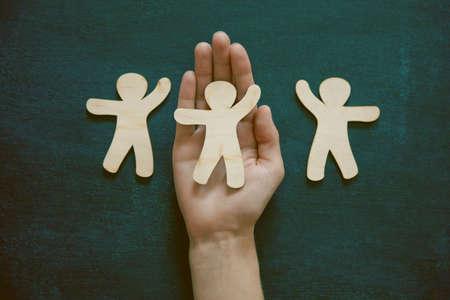 Foto de Hands holding little wooden men on blackboard background. Symbol of friendship, love or teamwork concept - Imagen libre de derechos