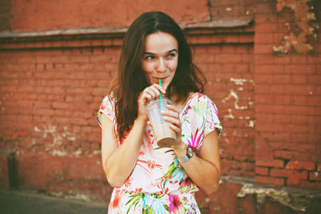 pretty smiling girl with milk shake on brick wall background
