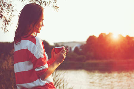 Photo pour pretty girl with morning coffee at river sunrise - image libre de droit