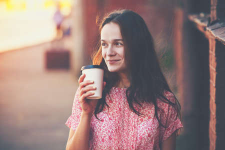 Foto de smiling pretty girl walking in street with morning coffee - Imagen libre de derechos