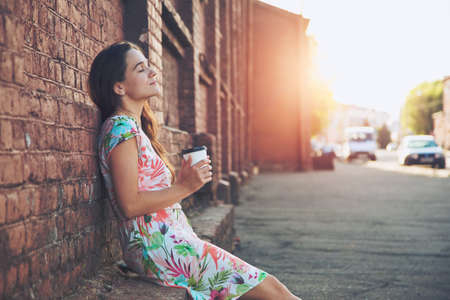 Foto de pretty girl sitting in street with morning coffee and relaxing - Imagen libre de derechos