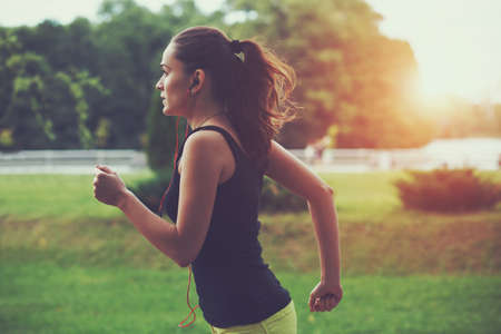 Photo pour Pretty sporty woman jogging at park in sunrise light - image libre de droit