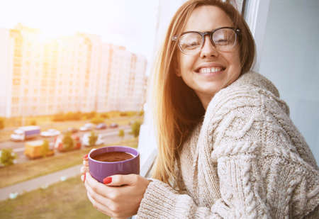 Foto de cheerful girl drinking coffee in morning sunlight in open window - Imagen libre de derechos