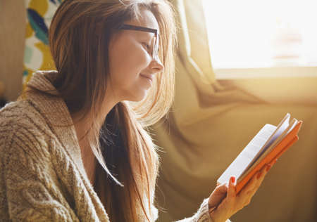 Photo for girl reading book at home in morning sunlight - Royalty Free Image