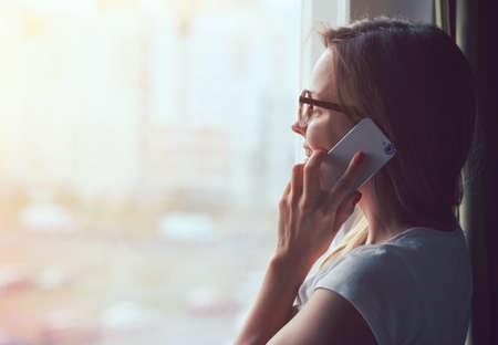 Foto de pretty woman talking on phone near window at home in morning sunlight - Imagen libre de derechos