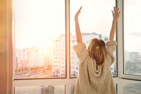 Photo pour Woman near window raising hands facing the sunrise at morning - image libre de droit