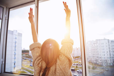 Foto de Woman near window raising hands facing the sunrise at morning - Imagen libre de derechos