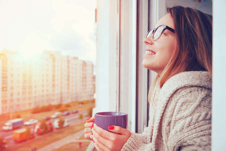 Photo pour cheerful girl drinking coffee in morning sunlight in open window - image libre de droit