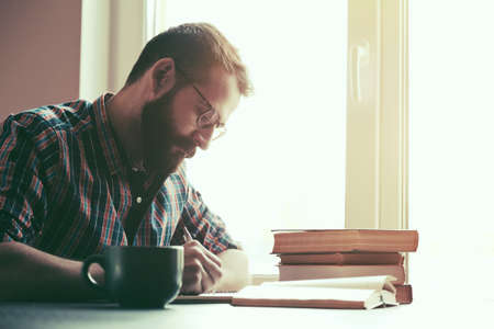 Photo pour Bearded man writing with pen and reading books at table - image libre de droit