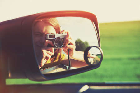Photo pour smiling girl taking photo with camera moving in car - image libre de droit