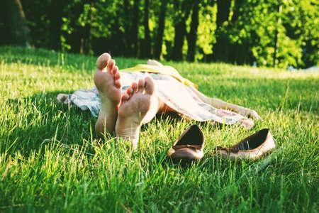 Foto de girl lying in grass barefoot without shoes in summer sun - Imagen libre de derechos