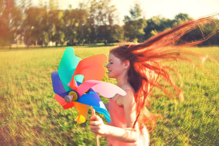 Photo for Happy redhead girl with pinwheel toy in motion blur. Freedom, summer, childhood concept - Royalty Free Image