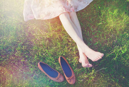 Photo pour girls legs lying in grass barefoot without shoes - image libre de droit