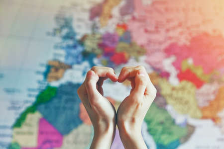 Foto de hand in heart shape with love on world map background - Imagen libre de derechos