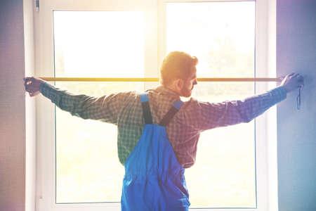 Photo pour service man installing window with measure tape - image libre de droit