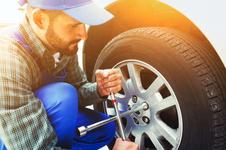 Foto de mechanic changing car tire with wheel wrench - Imagen libre de derechos