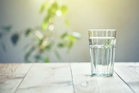 Foto de Glass of pure water on sunlight background with natural plant - Imagen libre de derechos